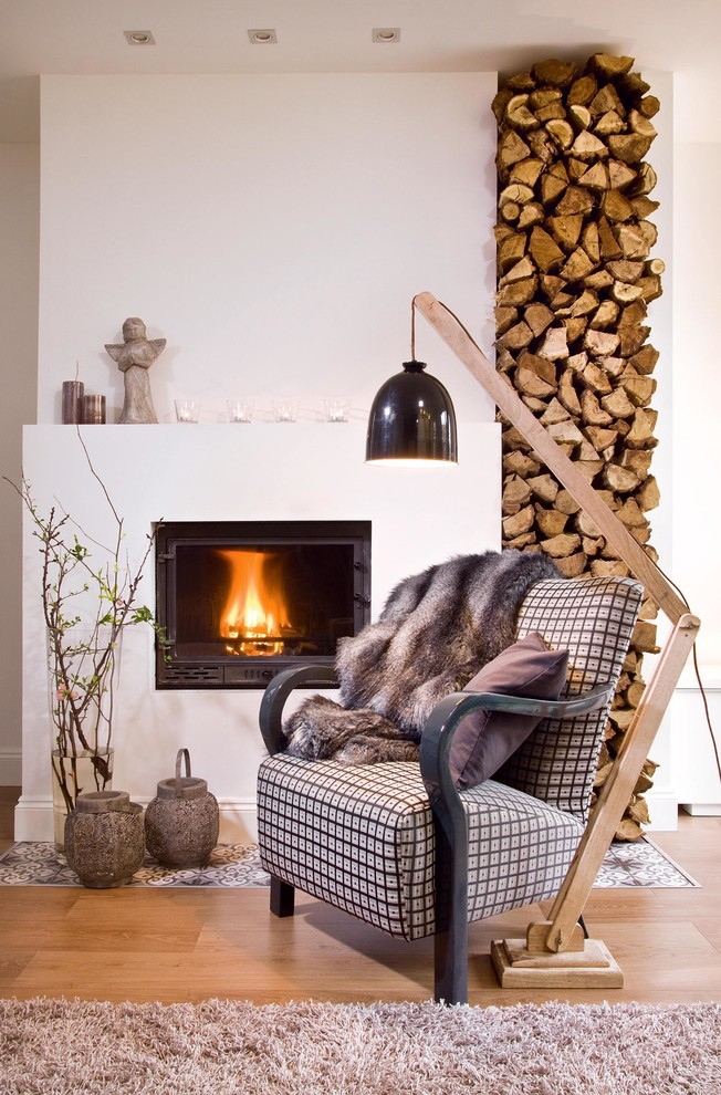 contemporary small living room wood stand floor lamp with black finish shade striped armchair with dark animal skinned blanket reclaimed wood floors a standard fireplace