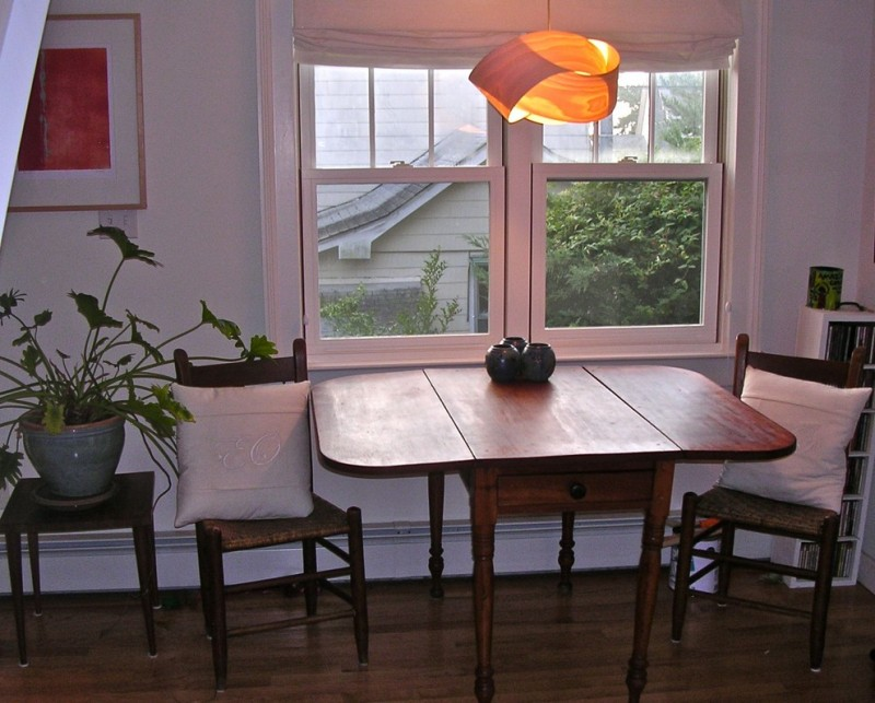 eclectic dining nook dark wood drop leaf table dark wood chairs with knitted wood seating low lighted statement pendant