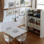 eclectic dining room white finish dining chairs and table with wood legs medium toned wood floors white painting walls with cluster of framed pictures shelving with concrete room partition