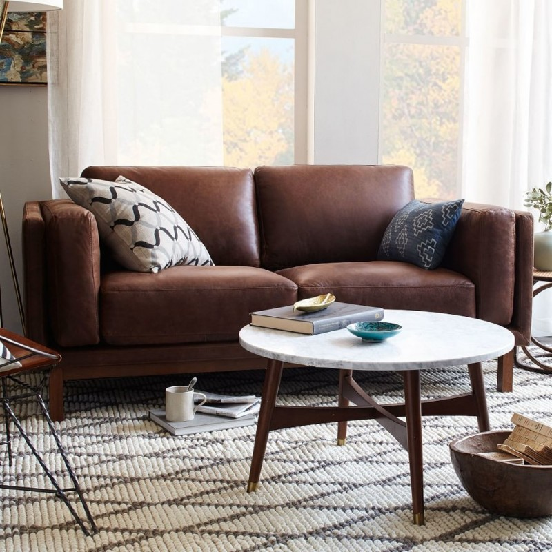 eclectic living room distressed coffee brown leather loveseat multicolored throw pillows mid century modern coffee table with white round top and angled legs