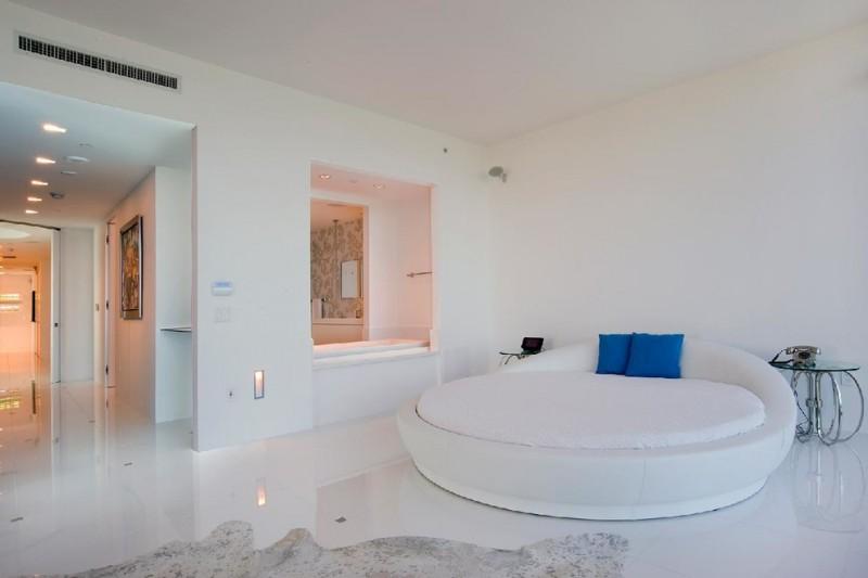 fairly white round platform bed blue throw pillows