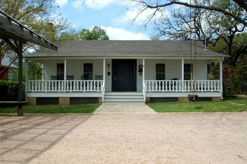 farmhous exterior and porch dark toned lattice skirting with diamond cut ventilators brick pillars white painted wood rails