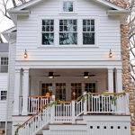 farmhouse exterior with white wood railings and higher skirting for storage unit