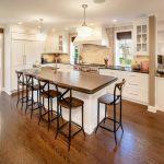 farmhouse kitchen idea medium toned wood kitchen island with undermount sink medium toned wood bar stools with back medium toned wood floors white kitchen cabinets