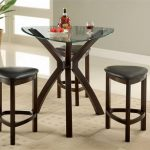 glass top triangle dining table with dark wood X legs black leather triangle stools with dark wood legs