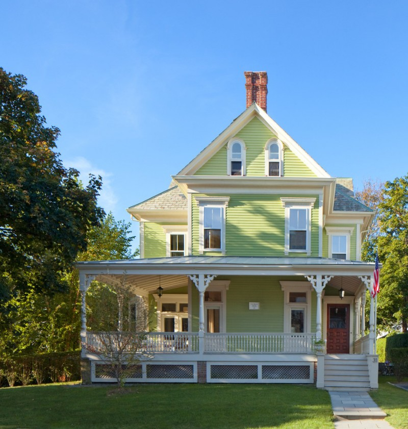 large victorian exterior in fresh green and white accent dark toned porch skirting with white frames
