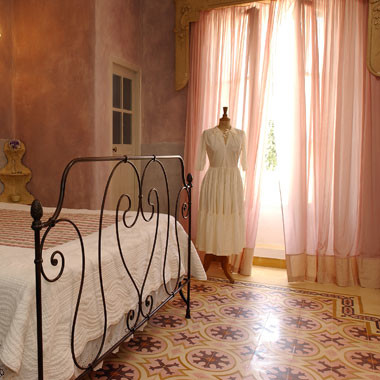mediterranean bedroom baby pink lace curtains deep pink wall painting classic bed frame in black stain vintage tiles in red with motifs