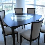 modern dining room triangle dining table with black finishing and additional glass center panel black framed dining chairs