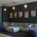 modern family room light grey floor couch navy blue ottomans white round top side table dark painted walls with colorful wall pictures a series of bulb pendants
