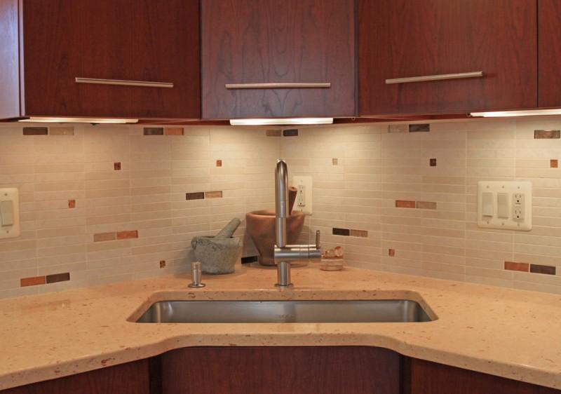 modern kitchen design larger stainless steel corner sink stainless steel faucet light toned tiles backsplash light toned countertop cherry wood cabinets