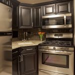 modern kitchen idea clean lined cut corner sink in deep biscuit color gold toned granite countertop black satin finished cabinets with silver handlers stainless steel appliances