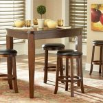 narrow triangle dining room with dark wood finishing black leather stools
