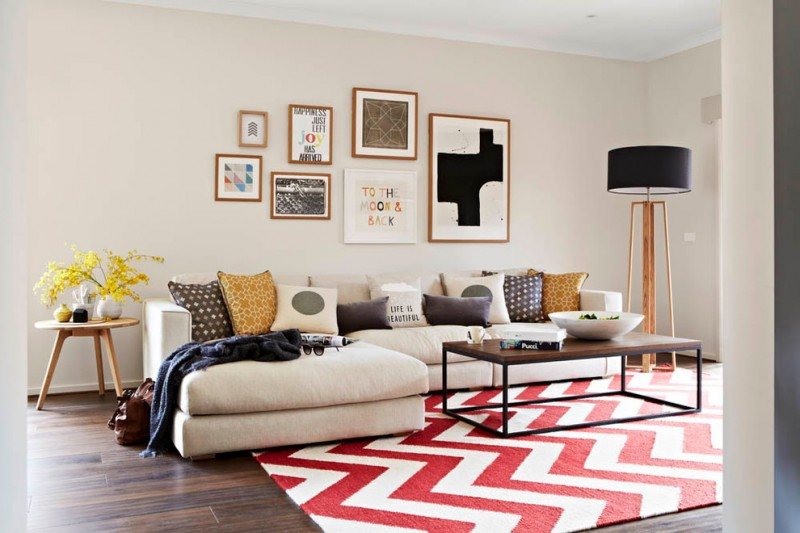 neutral painted walls with a cluster of wall arts neutral light couch with facing chasing multicolored throw pillows bright red white geometric rug dark wood floors round top wood side table