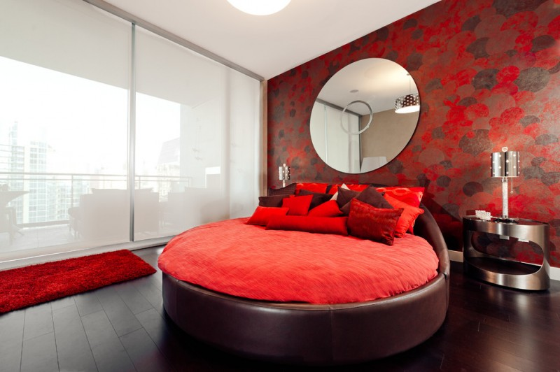 red elegant bedroom design brown round platform bed red round mattress red pillows red area rug red wallpaper with dark accents round decorative wall mirror stainless steel bedside tables