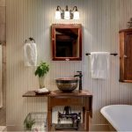 rustic bathroom idea antique drop leaf table as counter bronze sink long neck tap wood framed vanity mirror traditional vanity lamps white wood siding walls
