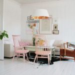 scandinavian living room pure white wall painting a cluster of wall pictures a couple of baby pink chairs white couch deep brown armchair cowhide rug huge pendant with inner orange shade