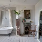 shabby chic bathroom design white bathtub with clawn feet vintage style narrow cabinet ornate fireplae wooden chair white painted wood board floors white subway tiled walls