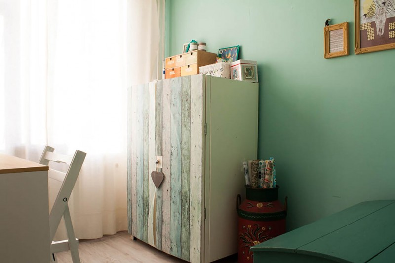 shabby chic wardrobe cabinet with vertical wood panelings green painted walls antique vase light toned wood floors