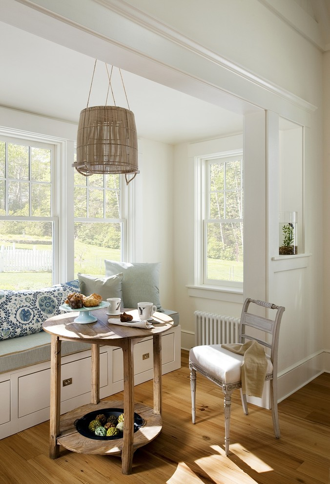 small beach style breakfast nook built in bench seat with storage round top wood table light toned wood chair medium toned wood floors white walls bay window