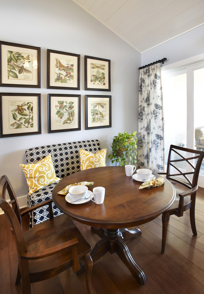small traditional breakfast corner black white banquette yellow throw pillows round top wood table wood chairs darker wood floors light blue painted walls well ordered wall arts