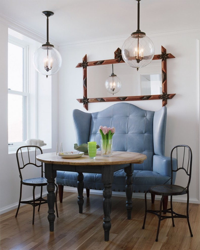 small traditional breakfast corner expensive blue banquette two smaller chairs in dark tone butcher block table with round top decorative mirror with crafted frame a couple of giant bulb pendants