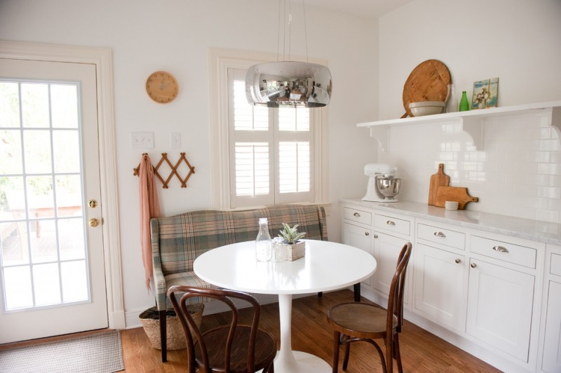 traditional breakfast nook wood chairs fabric covered banquette white kitchen counter with cabinets and upper shelving unit medium toned wood floors