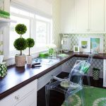 transitional home office L shaped working desk made of dark wood green area rug green office wallpaper built in white cabinets clear acrylic chairs