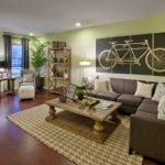 transitional living room vibrant green painting walls creative bicycle graphic soft dark couches wood coffee table neutral area rug reclaimed wood floors