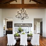 Tropical Dining Room White Dining Chair Slipcovers With Pleat Detail Reclaimed Wood Floors Black Wrought Iron Chandelier Dark Wood Dining Table