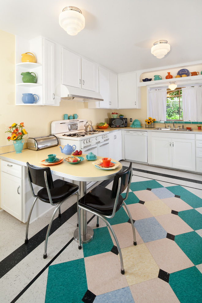 vintage tiles with pop of colors L shape kitchen counter with wood top and extended table for breakfast nook black dining chairs white kitchen cabinets