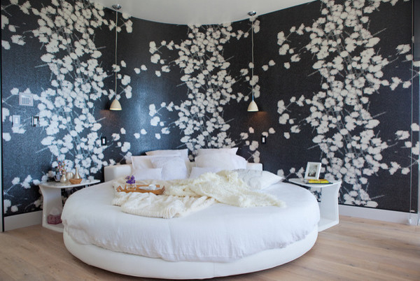 white round platform bed in contemporary style black white wallpaper light wood floors modern white bedside tables modern hang lamps