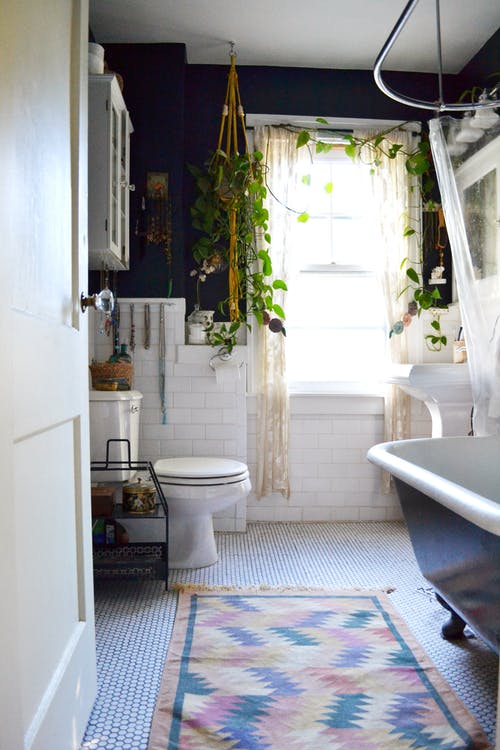 Bohemian bathroom idea colorful rug white mosaic tiled floors halfway dark painted wall halfway subway tiled wall in white clawfoot bathtub