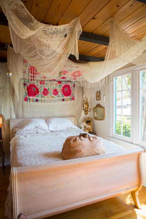 Bohemian bedroom design classic bed frame textural white bedding idea bold pink flowered background white bed curtains