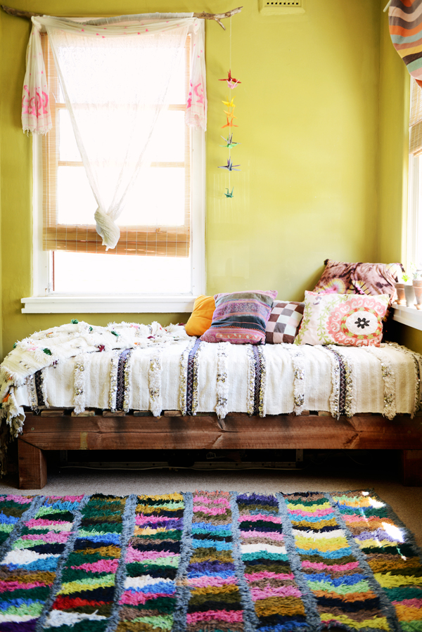 Bohemian inspired bedroom in minimalist look lemon yellow wall color wooden bed in smaller size textural bedding multicolored throw pillows colorful shag rug window with white transparent curtain