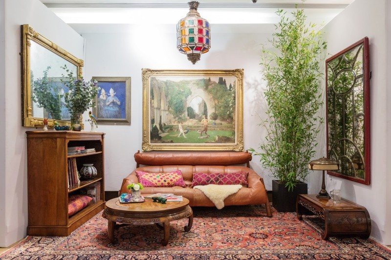 Bohemian living room idea brown leather sofa long & multicolored throw pillows ethnic area rug Moroccan pendant with colorful glass lampshade wooden round top Moroccan coffee table indoor plants
