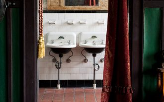 Bohemian look bathroom vintage bathroom cabinet with vintage mirror ethnic entrance carpet ethnic door curtain in red a couple of pedestal sinks subway tiled walls in white red tiled floors