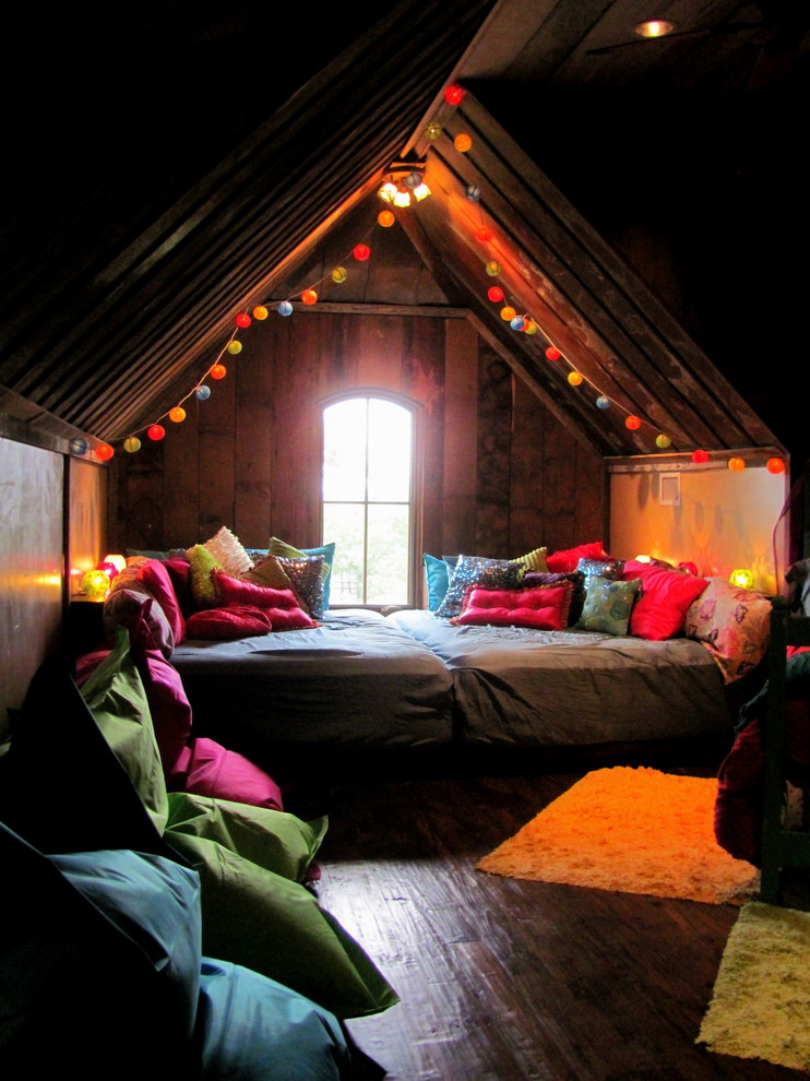 Bohemian style attic bedroom colorful string lamps center window with glass panel yellow shug rug colorful pillows