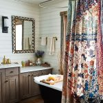 Bohemian Style Bathroom Idea White Painted Wood Siding Wall Mirror With Texural Frame Earthy Brown Cabinets With White Ceramic Countertop Black Bathtub Colorful Shower Curtain Hardwood Planks Flooring