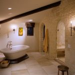 Mediterrenean Bathroom Design Light Toned Stone Walls White Concrete Wall Semi Corner Bathtub In White Light Toned Tiles Flooring Dark Wood Side Table With Round Top