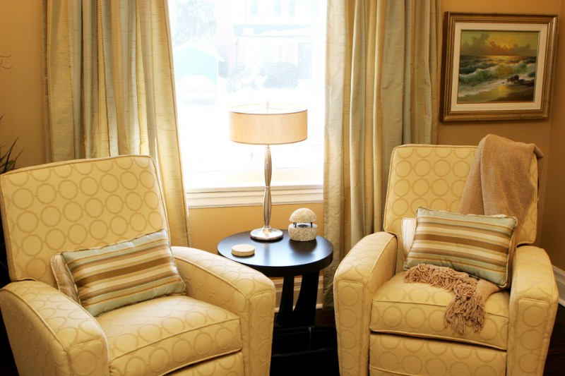 a couple of recliner chairs with circle patterns striped throw pillows black finished round top side table gold toned window curtains