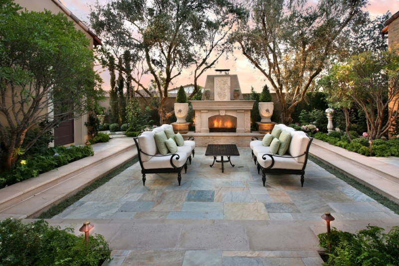 a pair of black wrought iron sofas with foams and throw pillows outdoor fireplace black wrought iron table soapstone tiled floors