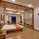 Airy And Large Bedroom Indian Inspired Wallpaper Wood Like Ceramic Floors Platform Bed With Tufted Headboard Lounge Sofa Glass Top Bedside Tables