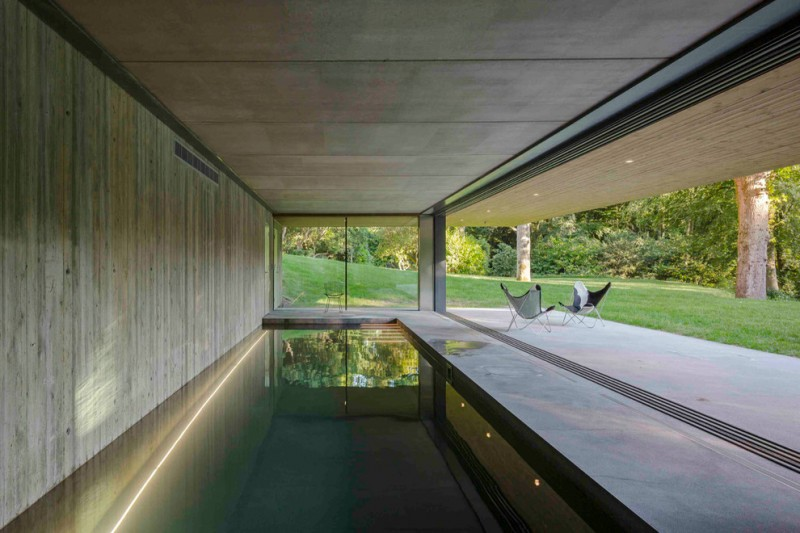 clean lined & modern indoor pool in dark shade concrete floors concrete toned wood planks wall clear glass windows without frames and trims