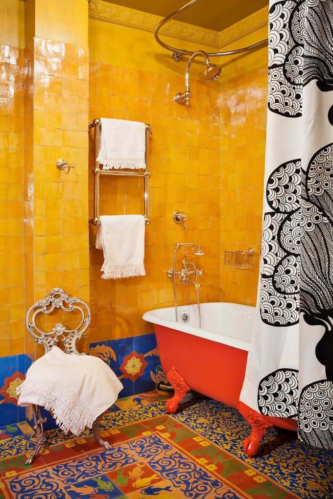 colorful Bohemian bathroom Mediterranean tiled floors red clawfoot tub bright orange tiled walls fabric shower curtain with patterns