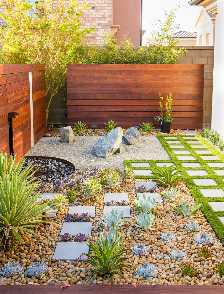 contemporary backyard idea with square shaped concrete pavings yellow natural stones succulents greengrass wood siding outdoor walls