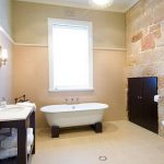 Contemporary Bathroom Design Exposed Stone Accent Wall In Warm Tone Warm Toned Walls White Bathtub With Dark Wood Feet