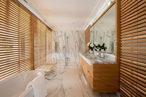 contemporary bathroom idea polished marble floors and walls wood lattice panels light wood floating vanity with wood framed mirror white bathtub modern tufted benches