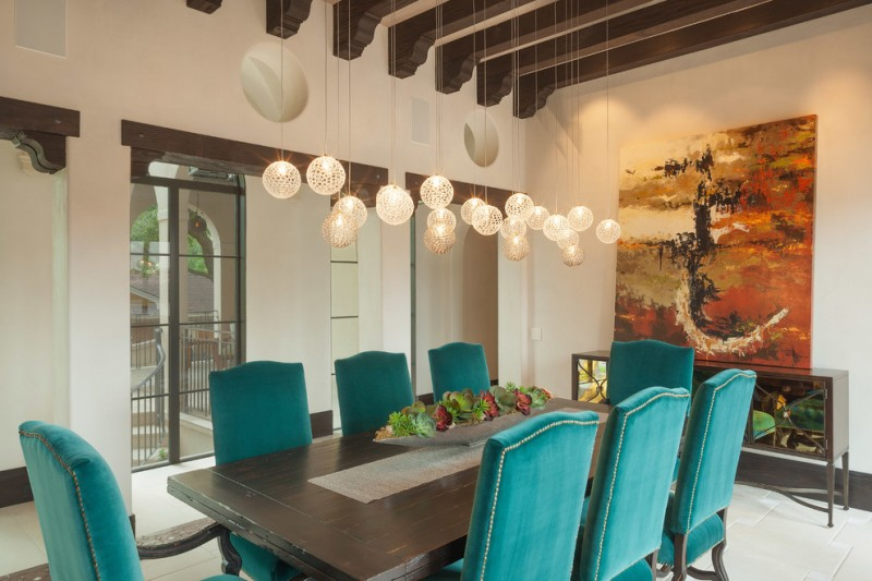 contemporary dining room a line of mini orb chandeliers with low lighted effect blue dining chairs black finished wood dining table centerpiece