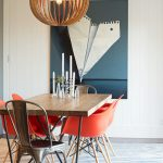 Contemporary Dining Space Wood Dining Table With Metal Legs Fun Red Dining Chairs Trendy & Big Pendant Giant Hand Painting For Wall Decor Striped Area Rug