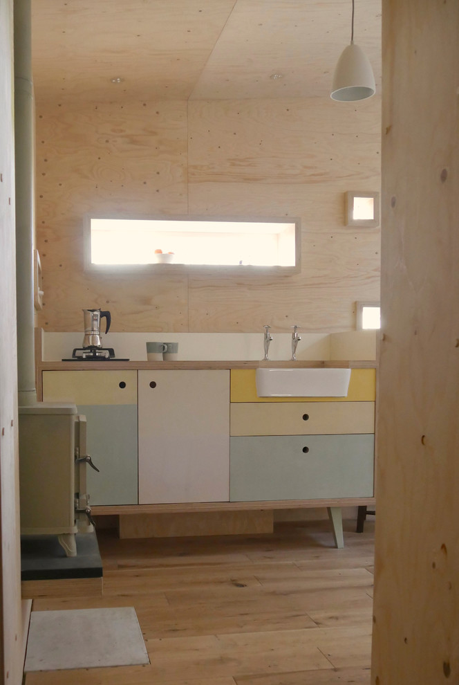 contemporary freestanding kitchen sink cabinet with pastel doors and farmhouse sink plywood wall panels light wood floors